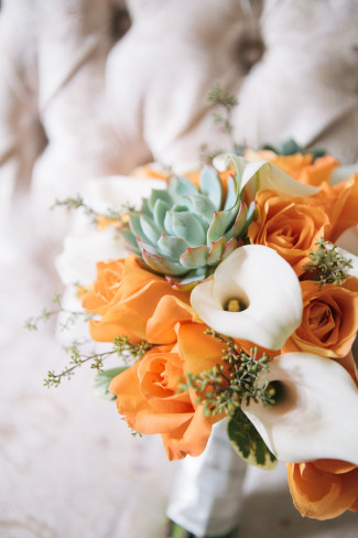Orange roses, green succulents and white lilies in bridal bouquet at Alder Manor House wedding