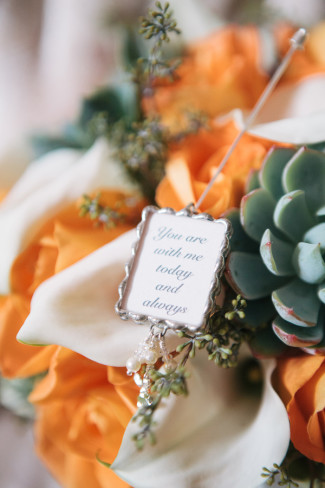 """Orange roses, green succulents and white lilies in bridal bouquet with a small frame attached with """"you are with me today and always"""""""