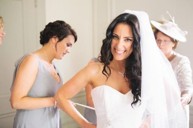 Bridesmaid wearing grey dress, helping tie corseted back of bride's dress.