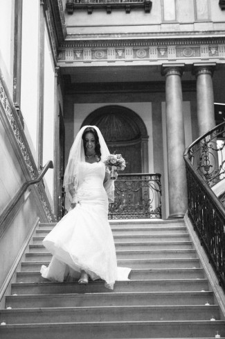 black and white photo of Bride walking down stairs at Alder Manor House in Westchester