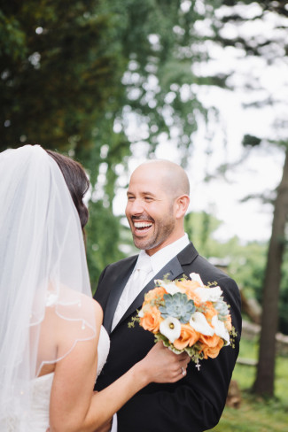 Bride wearing veil and carrying orange and green bouquet, seeing groom for first time before ceremony