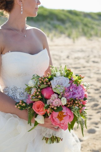 Bride holding a pink, white, peonies, berries bridal bouquet standing on the beach wearing drop earings