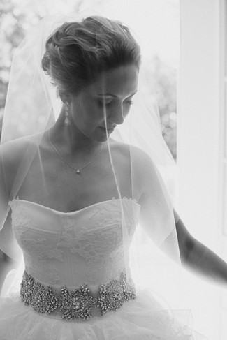Bride looking down while wearing a veil and rhinstone sash belt