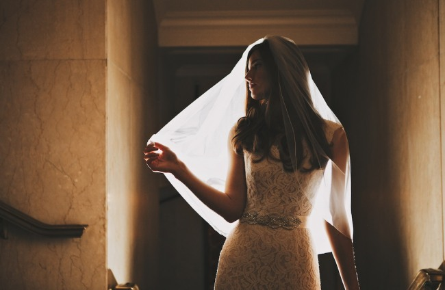Bride wearing a veil pulling it away from her face under a light