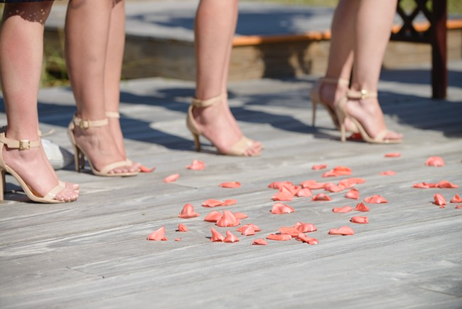 Bridesmaids wering gold ankle strap sandles standing on a wood deck with pink rose petals