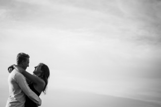 black and white photo of couple hugging with sky in the background