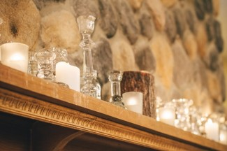 Crystal vases with whte candles on wood mantel for fall decor