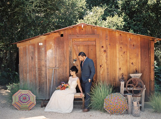 Indian bride sitting in front of wood shed with groom at holman ranch