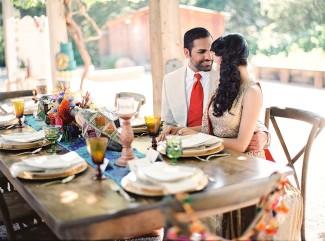 Indian bride and groom sitting at hindu themed wedding decor table at Holman ranch styled shoot