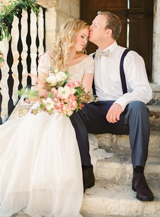 Kissing brides forhead seated on stairs at Holman Ranch