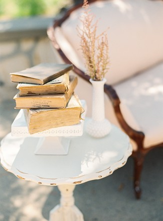 old books on side table at whimsical woodland love styled shoot
