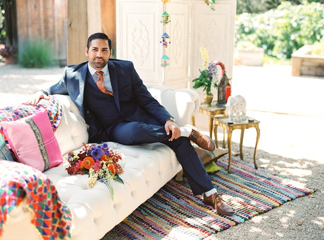 Indian groom in blue suit and orange tie sitting on white couch
