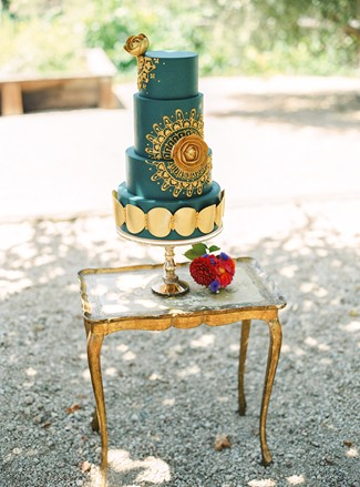 Green and gold ornate 4 tier wedding cake on cake stand