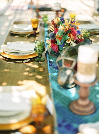 Wedding reception table with blue table runner, gold chargers and Moroccan lantern