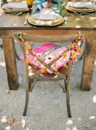 Wooden chair with pink cushion and yellow and pink tassels hanging