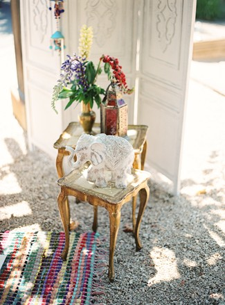 Gold table with glass elephant, Moroccan lantern and gold vase, red and cream flowers in front of wooden screen