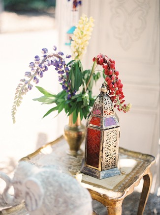Gold table with Moroccan lantern and gold vase with purple, red and cream flowers