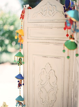 White wooden shutter screen with festive Hindu decorations hanging