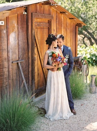 bride in front of wood shed with groom at holman ranch
