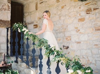 Exterior brick wall at Holman Ranch with bride on stairs
