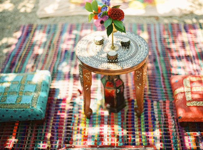 Moroccan/Indian picnic area with small gold ornate table, cushions and Moroccan lantern