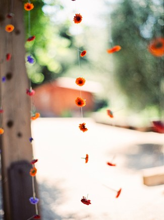 blue, red, and orange flowers hanging from string hanging from beam