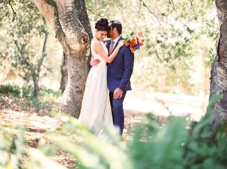 Indian bride wearing illusion bridal neckline dress holding blue, red and orange flower bouquet with groom