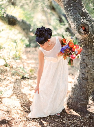 Indian bride wearing illusion bridal neckline dress holding blue, red and orange flower bouquet standing in the forest