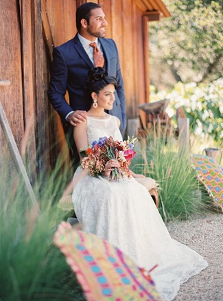 bride and groom pose in front of barn at Holman Ranch