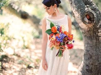 Indian bride wearing illusion bridal neckline dress holding blue, red and orange flower bouquet