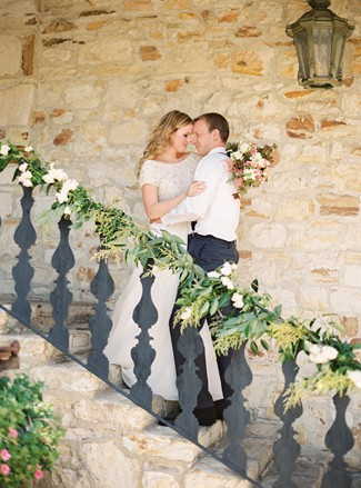 bride and groom embrace on stairs at Holman Ranch