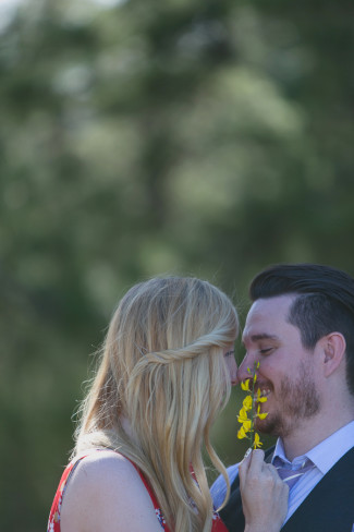 A couple nose to nose with the girl holding yellow buttercup flowers up to the guys face