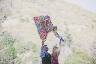A couple throwing a colorful quilt up in the air to spread it out together