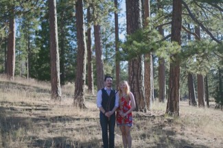 A couple standing side by side in the forest clasping their own hands