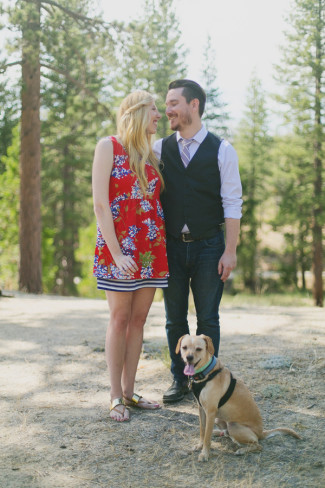 Couple standing together in the forest with their small tanned dog in front of them