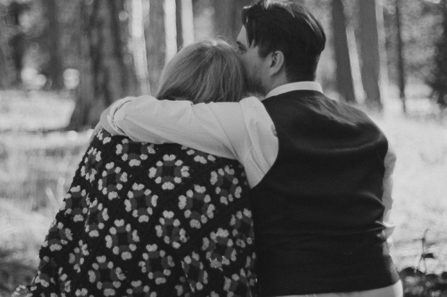 A couple sitting on the ground in the forest with a quilt and her husbands arm around her