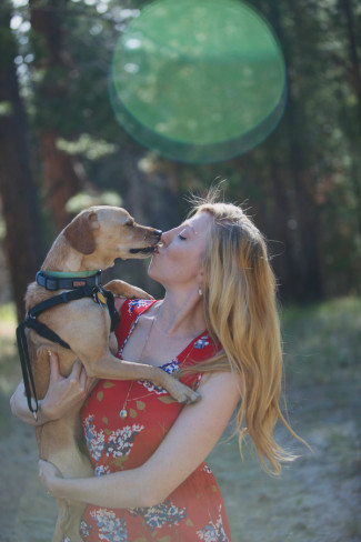 A girl wearing a red floral dress holding his small dog in the forest and letting him lick her face