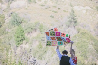 A couple throwing a colorful quilt up in the air to spread it out.