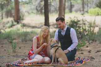 Couple hand feeding their dog treats while sitting on a colorful quilt in the forest