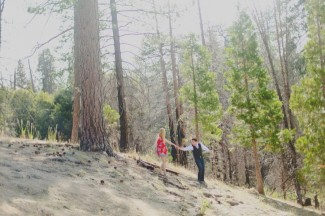 A couple walking in the forest with the guy reaching up to the girl helping her down the hill.
