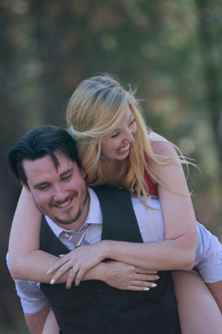 A guy wearing a white shirt and black vest carrying his wife on his back in the forest