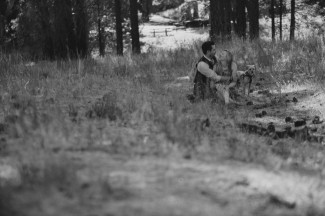 Black and white photo of a couple sitting in an open grass area of a forest with their dog.