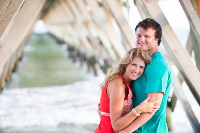 Engaged couple standing under a dock for fair and beach themed engagement shoot