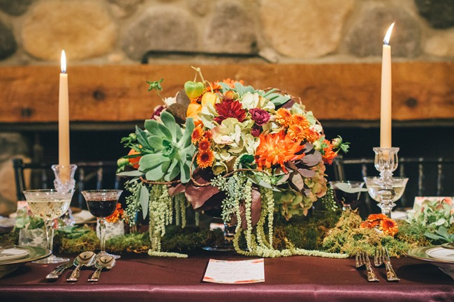 Fall reception centeriece with succulents, orange, white and red flowers, gold candles and red table cloth