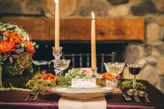 Fall reception place setting with purple table cloth , gold candles and gold dishes