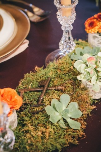 vintage keys lay on moss and succulent centerpiece