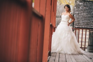 Bride wearing a strapless gown standing outside Fort Gibraltar in front of red building