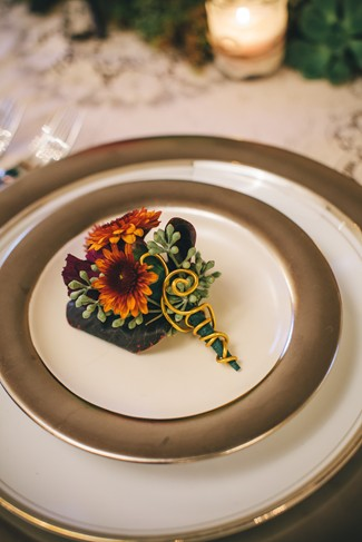 Gold rimmed plate with a bouttoniere in the center with orange, purple and green flowers