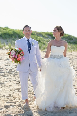 Groom wearing blue pin striped suit and holand bride wearing strapless ballgown standing on the beach