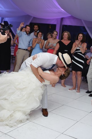 Groom wearing hat dunking bride on dance floor and kissing her